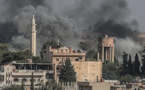 A picture taken from Turkish territory shows smoke rising from targets inside Syria during bombardment by Turkish forces at Ras al-Ayn town - Credit: REX