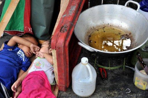 Homeless children sleep beside a frying pan at a street in Manila in January 2012