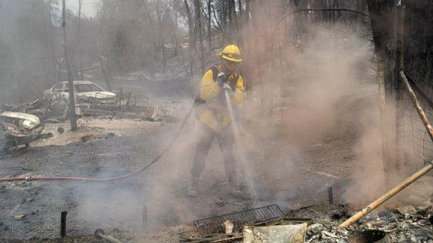 San Bernardino County Fire Department firefighter James Lippen hoses down hot spots left behind by a wildfire, Sunday, July 29, 2018, in Keswick, Calif. (AP)