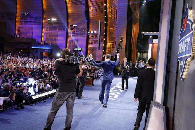 Johnny Manziel, from Texas A&M, celebrates as he walks onstage after being selected 22nd overall by the Cleveland Browns during the first round of the NFL football draft, Thursday, May 8, 2014, at Radio City Music Hall in New York. (AP Photo/Jason DeCrow)