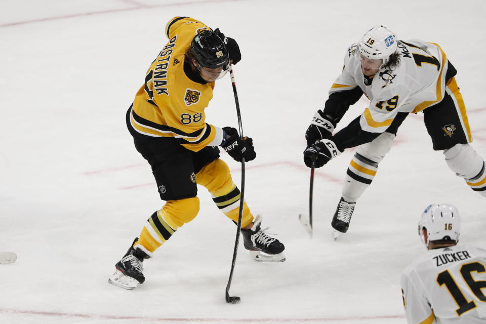 Boston Bruins' David Pastrnak lets go with a shot past Pittsburgh Penguins' Jared McCann during the first period of an NHL hockey game Saturday, April 3, 2021, in Boston. (AP Photo/Winslow Townson)