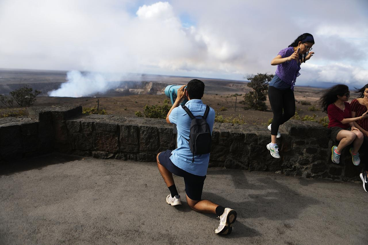 <p>Locals watch on as smoke billows from the top of the Kilauea volcano (Getty) </p>