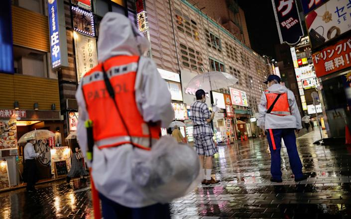 Security personnels of Toshima Ward conduct a reminder announcement to promote measures against the coronavirus on the street in Tokyo - REUTERS