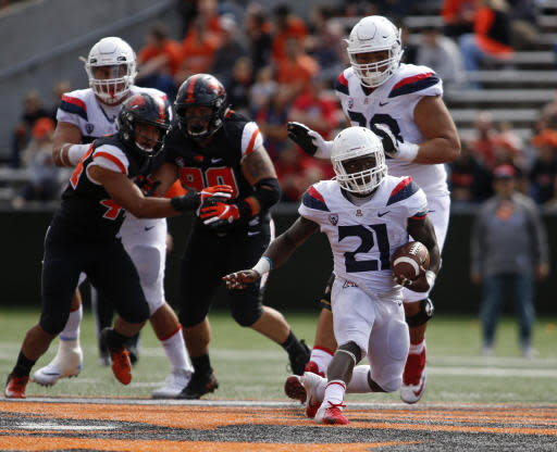 Arizona running back J.J. Taylor (21) breaks through the line for a gain in the third quarter of an NCAA college football game against Oregon State in Corvallis, Ore., Saturday, Sept 22, 2018. Arizona won 35-14. (AP Photo/Timothy J. Gonzalez)