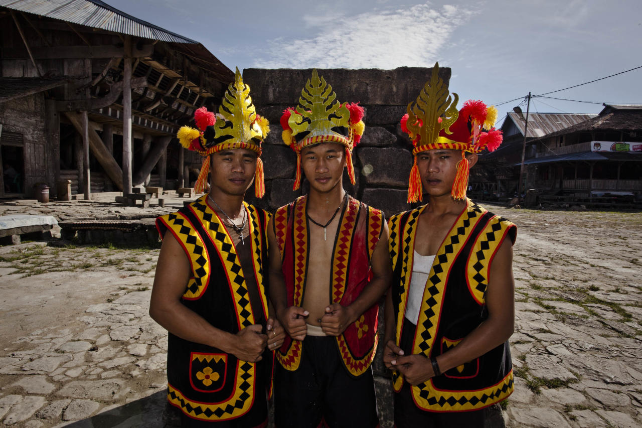 NIAS ISLAND, INDONESIA - FEBRUARY 22:  A villagers wearing traditional costume pose in front of a stone tower in Bawomataluwo village on February 22, 2013 in Nias Island, Indonesia. Stone Jumping is a traditional ritual, with locals leaping over large stone towers, which in the past resulted in serious injury and death. Stone jumping in Nias Island was originally a tradition born of the habit of inter tribal fighting on the island of Nias.  (Photo by Ulet Ifansasti/Getty Images)