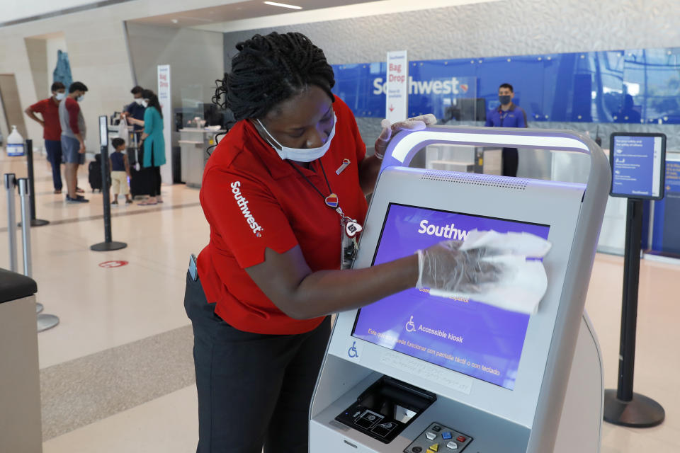 In this June 24, 2020, photo, Southwest Airlines employee, La Toya Malone Key wipes down a kiosk after it was used by a passenger to secure their boarding pass at Love Field in Dallas. (AP Photo/Tony Gutierrez, File)
