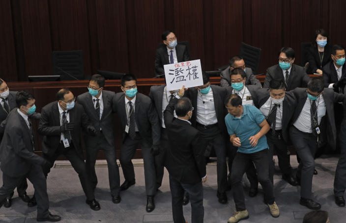 FILE - In this Monday, May 18, 2020, file photo, pro-democracy lawmaker Wu Chi-wai, right in green shirt, scuffles with security guards during a Legislative Council's House Committee meeting in Hong Kong. After nearly three decades in politics, the 58-year-old Wu, chairman of Hong Kong's largest pro-democracy party, is stepping down Monday, Nov. 30, 2020. All 15 lawmakers in the pro-democracy camp have decided to resign to protest a Beijing resolution in early November that led to the disqualifications of four of their colleagues. (AP Photo/Vincent Yu, File)