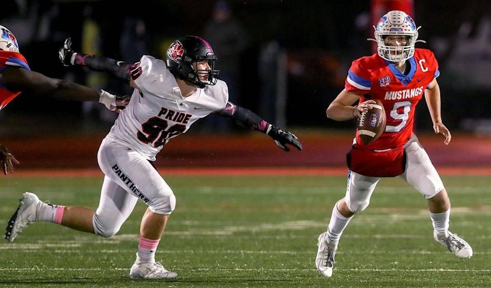 Grapevine quarterback Austin Alexander (9) tries to scramble away from Colleyville Heritage defensive lineman Taylor Steele (90) during the first haif, Friday night, October 25, 2019 played at Mustang-Panther Stadium in Grapevine, TX.