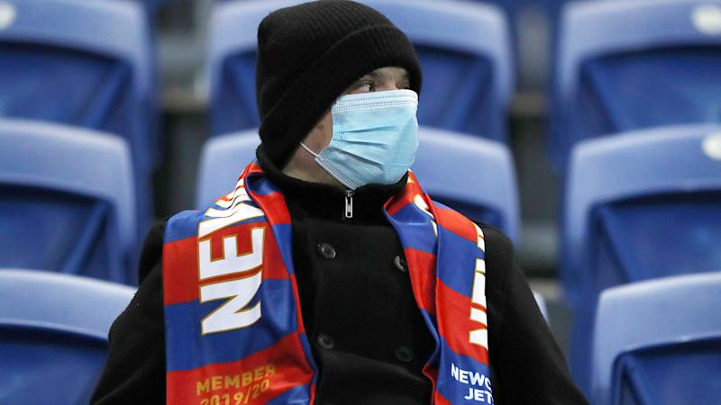 A Newcastle Jets fan, pictured here wearing a face mask during the match against Western United.