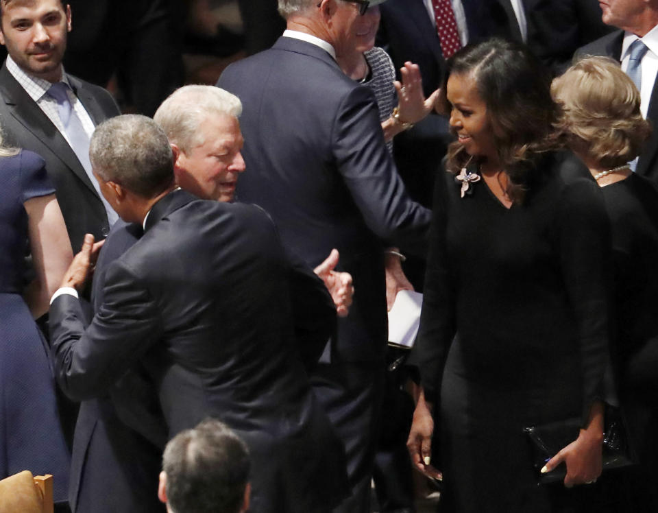 Former President Barack Obama hugs former vice president Al Gore as former first lady Michelle Obama watches before the memorial services for Sen. John McCain, R-Ariz., at Washington National Cathedral in Washington, Saturday, Sept. 1, 2018. McCain died Aug. 25, from brain cancer at age 81. (AP Photo/Pablo Martinez Monsivais)