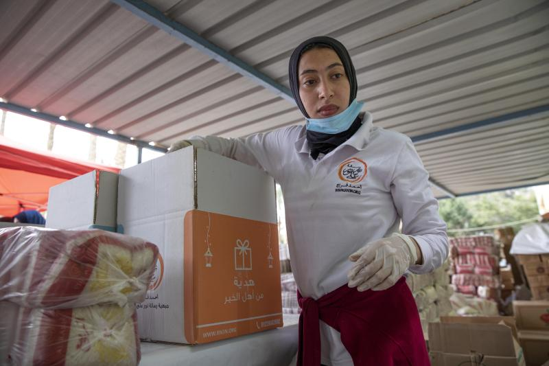 Non-governmental organization Resala Nour Ala Nour workers prepare cartons filled with food to distribute to people who have been greatly affected by the coronavirus outbreak, in Cairo, Egypt, Thursday, April 9, 2020. (AP Photo/Nariman El-Mofty)