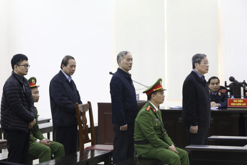 Vietnamese former minister of information and communication Nguyen Bac Son, right, former Mobifone Chairman Le Nam Tra, second right, former Minister of information and communication Truong Minh Tuan, second left, and valuer Hoang Duy Quang, left, stand as judge reads the verdicts at their trial in Hanoi, Vietnam Saturday, Dec. 28, 2019. Hanoi court on Saturday sentenced Son to life imprisonment in a multi-million dollar corruption case that also saw another minister and a dozen executives receive lengthy prison terms. (Nguyen Van Diep/VNA via AP)