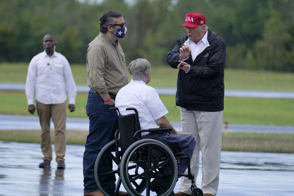 President Donald Trump talks with Texas Gov. Greg Abbott and Sen. Ted Cruz, R-Texas, as he arrives to view damage caused by Hurricane Laura, Saturday, Aug. 29, 2020, in Orange, Texas. (AP Photo/Alex Brandon)