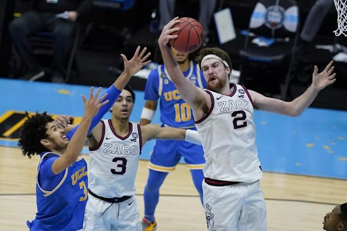 Gonzaga forward Drew Timme (2) grabs a rebound over UCLA guard Johnny Juzang (3) during overtime in a men's Final Four NCAA college basketball tournament semifinal game, Saturday, April 3, 2021, at Lucas Oil Stadium in Indianapolis. (AP Photo/Darron Cummings)