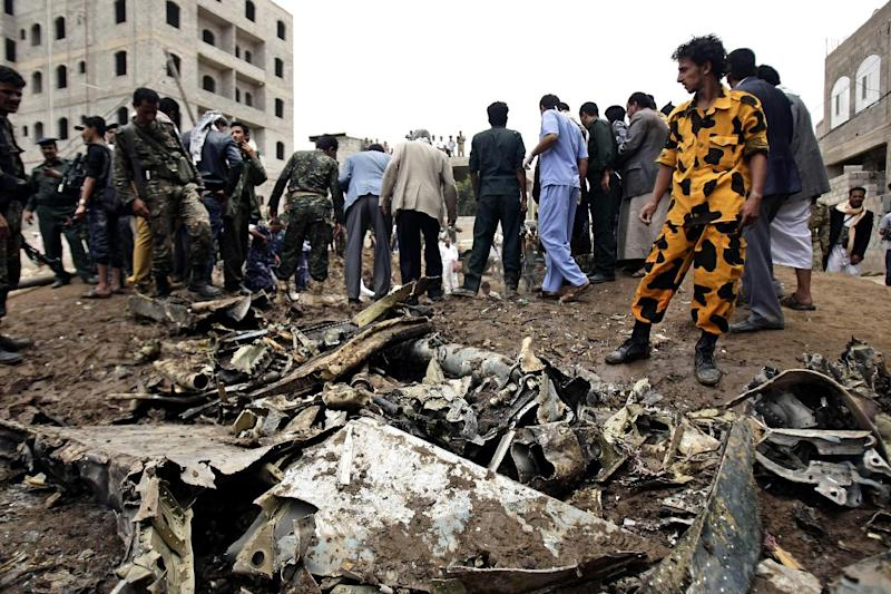 Yemeni security forces and soldiers gather at the site of a plane crash in Sanaa, Yemen, Monday, May 13, 2013. A Yemeni military plane on a training exercise crashed Monday in the country's capital, slamming into a residential neighborhood and setting at least four houses ablaze, according to a military official and an Associated Press reporter at the scene. (AP Photo/Hani Mohammed)