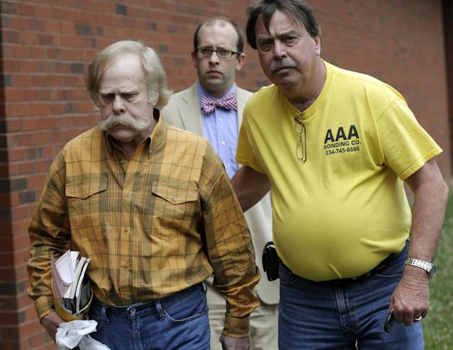 FILE - In this June 10, 2013, file photo, Harvey Updyke, left, departs the Lee County Justice Center in Opelika, Ala., with his bail bondsman and his attorney. The state's football fervor drew plenty of attention after the 2010 Iron Bowl, when Updyke, an Alabama fan, poisoned Auburn's two iconic oak trees at Toomer's Corner, whose branches were decorated with toilet paper during victory celebrations for decades. (AP Photo/Dave Martin, File)