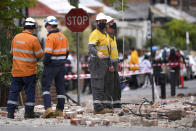 Emergency workers survey damage in Melbourne, Australia, where debris is scattered on a road after part of a wall fell from a building during an earthquake, Wednesday, Sept. 22, 2021. A strong earthquake caused damage in the city of Melbourne in an unusually powerful temblor for Australia, Geoscience Australia said. (James Ross/AAP Image via AP)