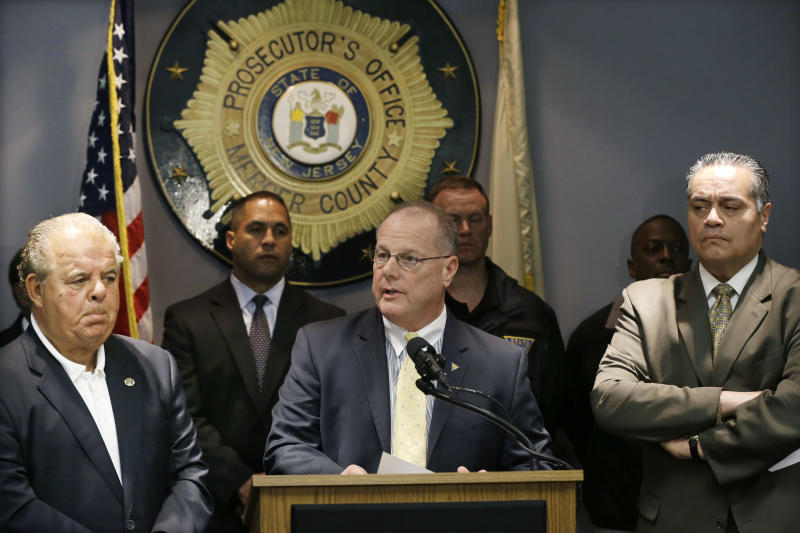 Mercer County Prosecutor Joseph L. Bocchini Jr., left, and Trenton Police Director Ralph Rivera Jr., right, listen in Trenton, N.J., Sunday, May 12, 2013, as New Jersey State Police Superintendent Col. Rick Fuentes answers a question after announcing that Gerald Tyrone Murphy, 38, had been shot by police and later died after a standoff with police. Three children held by Murphy are safe after a 36-hour standoff in Trenton ended early Sunday. Fuentes said officers made an entry into the room where the hostages were being held, and a single shot was fired at the suspect as he made a violent move toward one of the children. (AP Photo/Mel Evans)