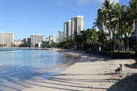 FILE - In this Oct. 2, 2020, file photo, a man sits on Waikiki Beach in Honolulu. Honolulu is loosening some restrictions on social activity now that more than half its population has been vaccinated against COVID-19. The new rules allow outdoor social gatherings of up to 25 people and indoor gatherings of up to 10.(AP Photo/Caleb Jones, File)