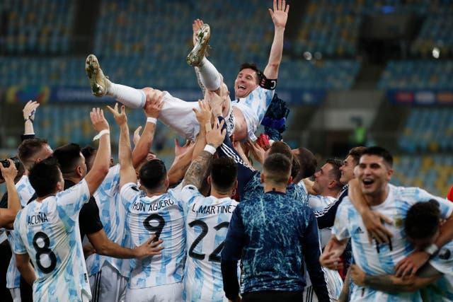 Lionel Messi is thrown in the air by his team-mates