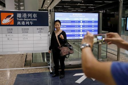 A passenger poses with train schedules during the first day of service of the Hong Kong Section of the Guangzhou-Shenzhen-Hong Kong Express Rail Link, in Hong Kong, China September 23, 2018. REUTERS/Tyrone Siu
