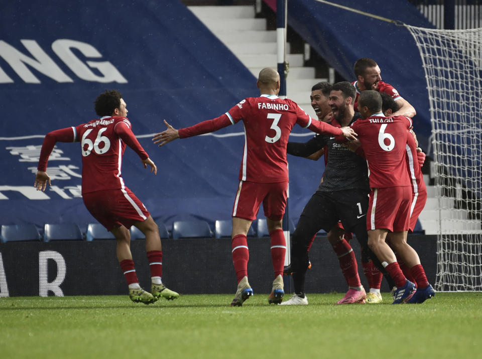 Liverpool's goalkeeper Alisson celebrates with teammates after scoring his side's second goal during the English Premier League soccer match between West Bromwich Albion and Liverpool at the Hawthorns stadium in West Bromwich, England, Sunday, May 16, 2021. (AP Photo/Rui Vieira, Pool)