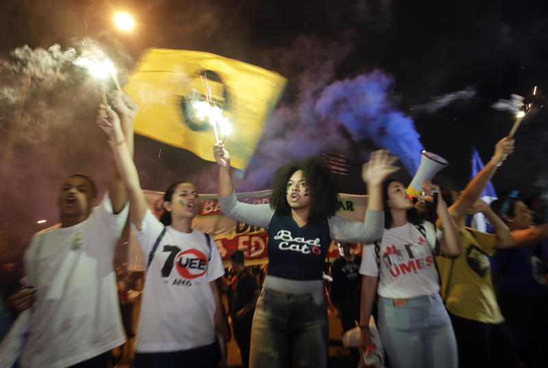 Students light flares as they protest against a massive cut in the education budget imposed by the administration of Brazilian President Jair Bolsonaro in Sao Paulo, Brazil, Wednesday, May 15, 2019. Federal education officials this month announced budget cuts of $1.85 billion for public education, part of a wider government effort to slash spending. (AP Photo/Andre Penner)
