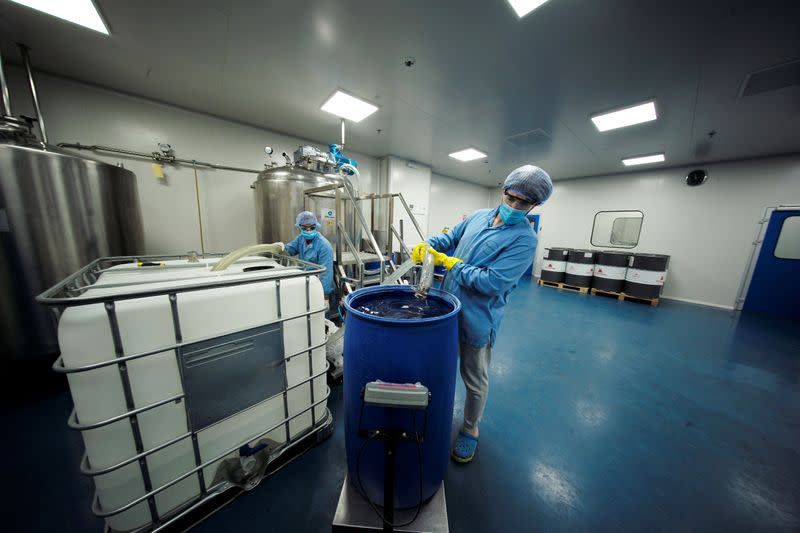 Employees mix chemicals into a steamer tank to make hand-sanitizers at Dhaman Medical Company, following the outbreak of the coronavirus disease (COVID-19), in Hidd