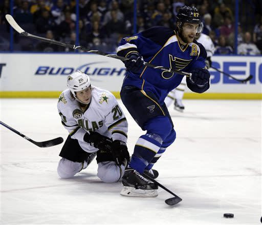 Dallas Stars' Cody Eakin, left, reaches between the legs of St. Louis Blues' Alex Pietrangelo for a loose puck the during the first period of an NHL hockey game on Friday, April 19, 2013, in St. Louis. (AP Photo/Jeff Roberson)