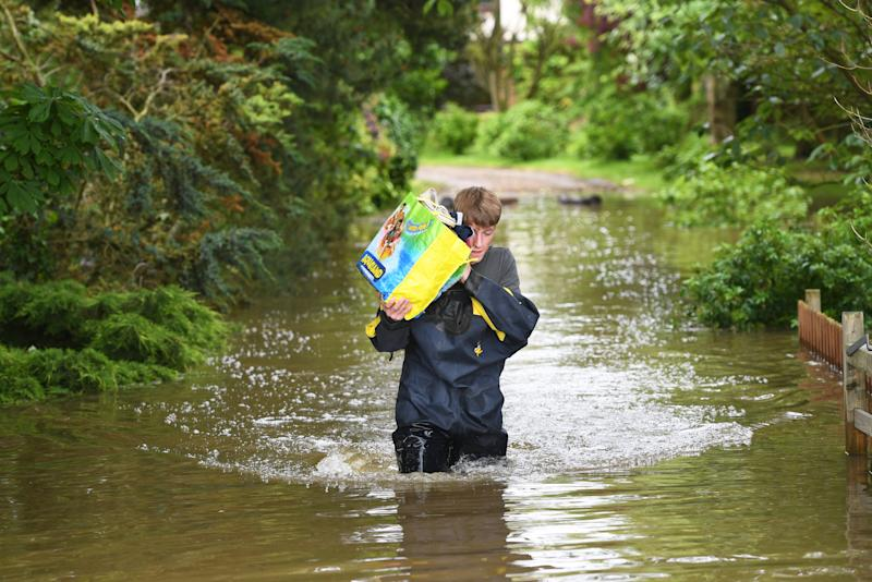 A man wades through floodwater in Wainfleet All Saints, in Lincolnshire (Joe Giddens/PA Wire)