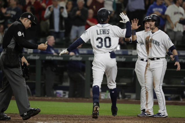 Seattle Mariners' Kyle Lewis (30) greets Austin Nola, right, and Kyle Seager after Seager and Nola scored on a three-run home run by Lewis during the seventh inning of a baseball game against the Cincinnati Reds, Wednesday, Sept. 11, 2019, in Seattle. Lewis ended a no-hitter by Reds starting pitcher Sonny Gray. (AP Photo/Ted S. Warren)