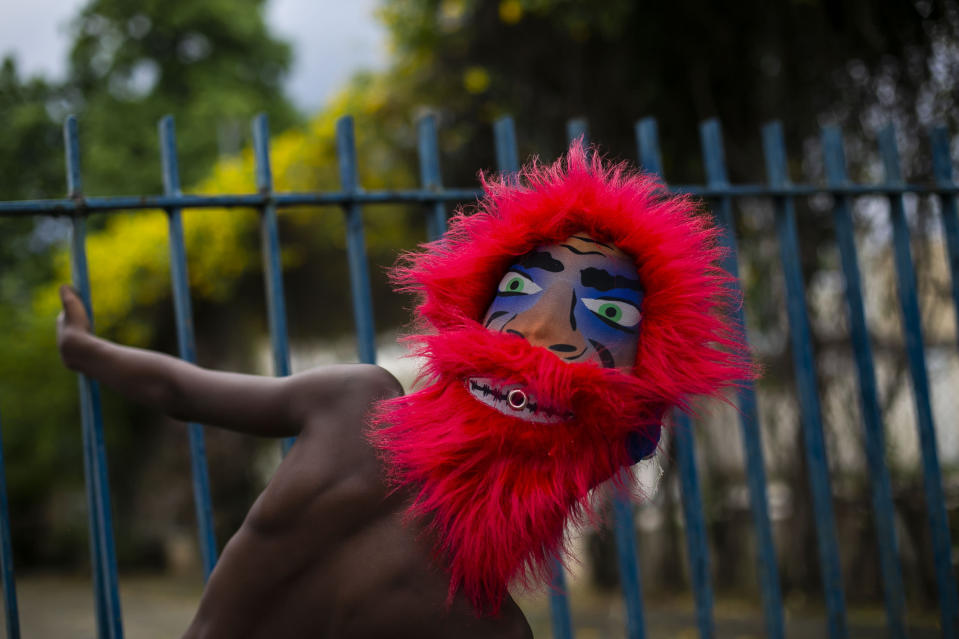 """A member of a """"bate-bola"""" or ball hitters group - men who dress up in exuberant, identical, hand-made costumes known as """"fantasias"""" - makes a brief appearance as part of a Carnival tradition despite restrictions due to the new coronavirus pandemic, in Rio de Janeiro, Brazil, Saturday, Feb. 13, 2021. Rio's city government officially suspended Carnival and warns it will have no tolerance for those who try to celebrate with open street parades or clandestine parties. (AP Photo/Bruna Prado)"""