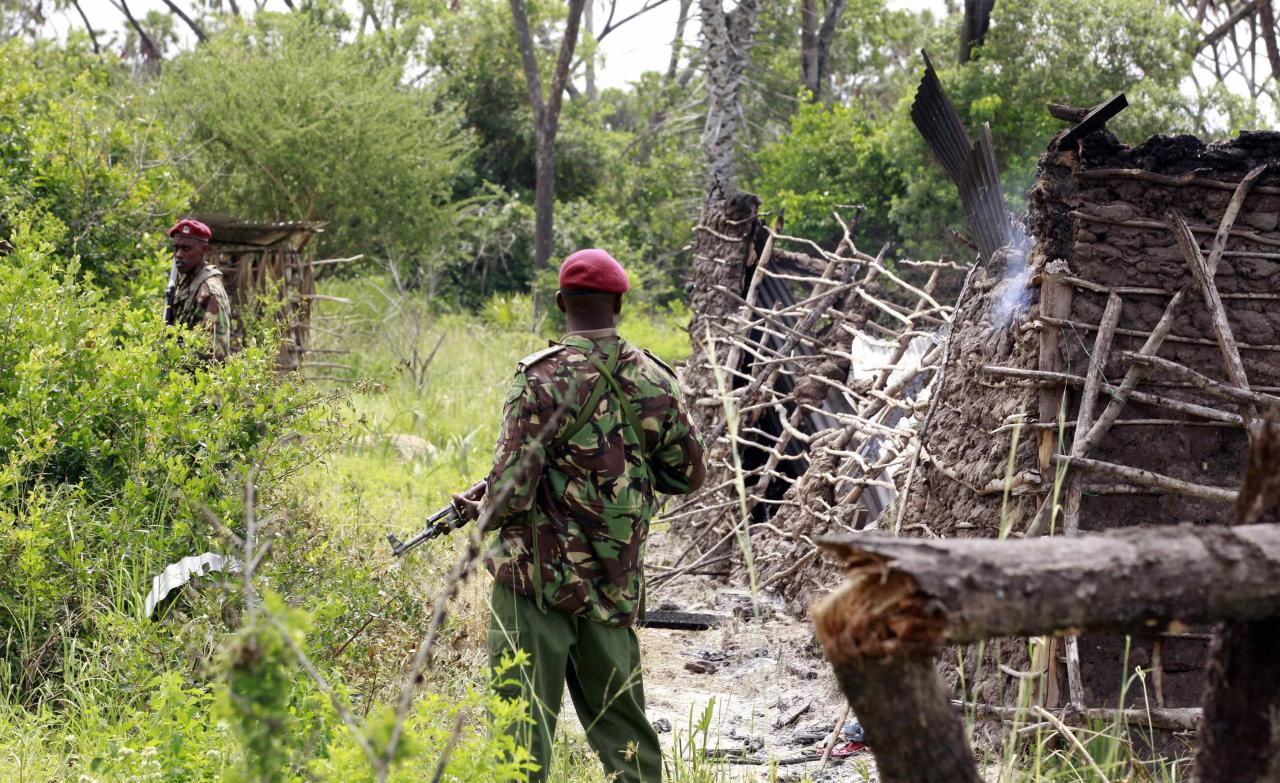 Policemen stand guard at a homestead after gunmen attacked Hindi village, near Kenya's coastal town of Lamu, July 6, 2014. Gunmen killed at least 29 people in raids on two separate areas on the Kenyan coast, the interior ministry said on Sunday. The Somali Islamist militant group al Shabaab said it had staged an attack on Saturday evening in the coastal area. Nine people lost their lives at the Hindi trading centre in Lamu county, near the scene of attacks in which 65 people were killed last month, Mwenda Njoka, the ministry's spokesman told Reuters. REUTERS/Joseph Okanga (KENYA - Tags: CIVIL UNREST CRIME LAW)