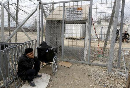 Stranded wheelchair-bound Zhino Hasan, 17, and her father Sarkawt wait in front of a closed border gate at Idomeni, hoping that Macedonia would relent and allow her and her family to resume their northward trek through the Balkans to Germany, February 26, 2016. REUTERS/Yannis Behrakis