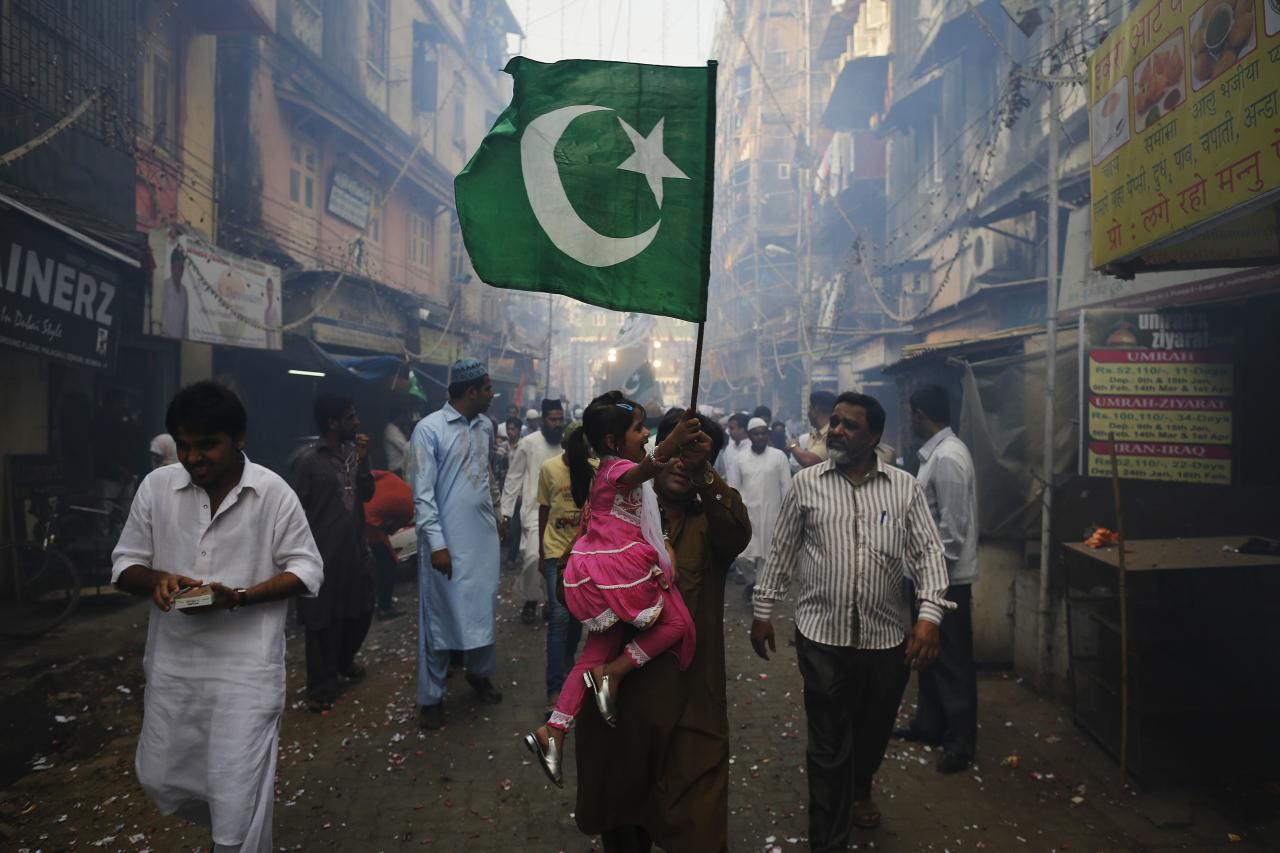 A man and his daughter wave an Islamic religious flag they participate in a procession to mark Eid-e-Milad-ul-Nabi, or birthday celebrations of Prophet Mohammad in Mumbai January 14, 2014. REUTERS/Danish Siddiqui (INDIA - Tags: RELIGION SOCIETY)