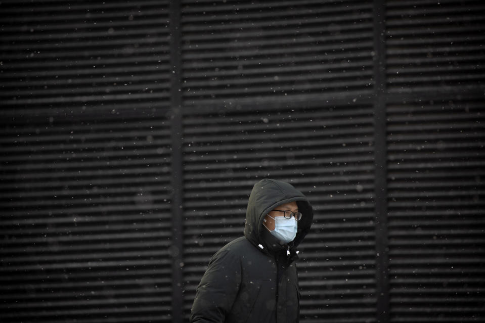 A man wearing a face mask to protect against the spread of the coronavirus walks along a street during a snowy morning in Beijing, Tuesday, Jan. 19, 2021. A Chinese province near Beijing grappling with a spike in coronavirus cases is reinstating tight restrictions on weddings, funerals and other family gatherings, threatening violators with criminal charges. (AP Photo/Mark Schiefelbein)
