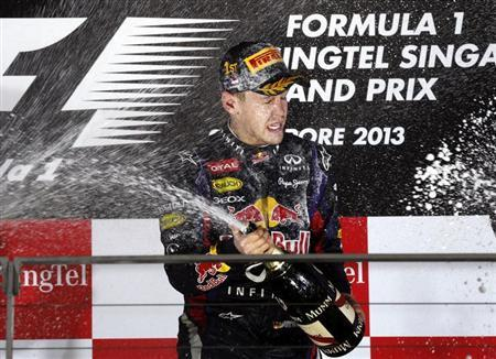 Red Bull Formula One driver Sebastian Vettel of Germany sprays champagne on the podium after winning the Singapore F1 Grand Prix at the Marina Bay street circuit in Singapore September 22, 2013. Vettel cruised to a third straight Singapore Grand Prix victory on Sunday and moved closer to a fourth consecutive Formula One world title with a dominant drive under the floodlights at the Marina Bay Street Circuit. REUTERS/Pablo Sanchez