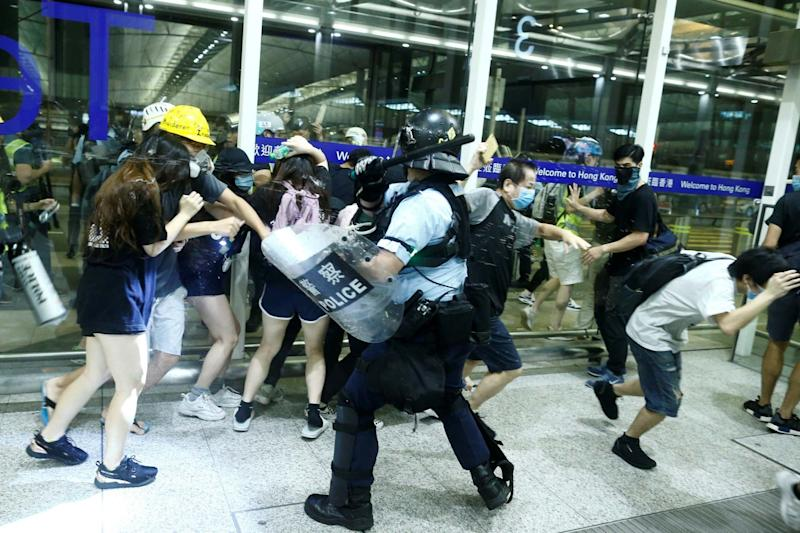 Police clash with anti-government protesters at the airport in Hong Kong (REUTERS)