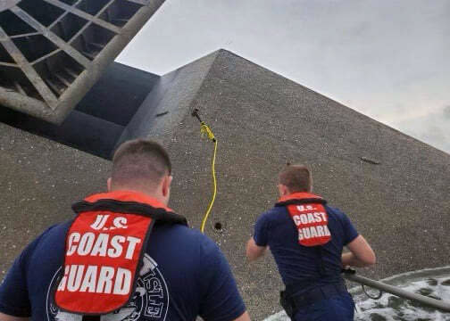In this photo provided by the U.S. Coast Guard, Coast Guard Station Grand Isle 45-foot Response Boat-medium boat crew members attempt to throw a hammer at the hull of the SeaCor Power. The crew was attempting to make contact with potential survivors inside the vessel. . The Seacor Power, an oil industry vessel, flipped over Tuesday, April 13, 2021 in a microburst of dangerous wind and high seas. (U.S. Coast Guard via AP)
