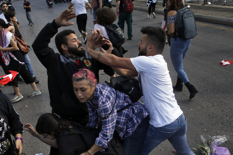 A Hezbollah supporter, right, clashes with an anti-government protester, left, during a protest in Beirut, Lebanon, Tuesday, Oct. 29, 2019. Beirut residents have scuffled with Lebanese protesters blocking a main thoroughfare, prompting riot police to move to separate them. The tension Tuesday comes on the 13th day of anti-government protests. (AP Photo/Bilal Hussein)