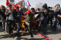 Pro-king supporters clash with riot police as they march demanding reinstating monarchy that was abolished more than a decade ago in Kathmandu, Nepal, Monday, Jan.11, 2021. Monday's protest was the latest anti-government protest against Prime Minister Khadga Prasad Oli who has been facing street demonstrations against him from a splinter faction of his own Communist party and more from opposition political groups for dissolving parliament. Nepal's centuries-old monarchy was abolished in 2008 by the parliament and replaced by a republic where the president was elected as the head of state. (AP Photo/Niranjan Shrestha)