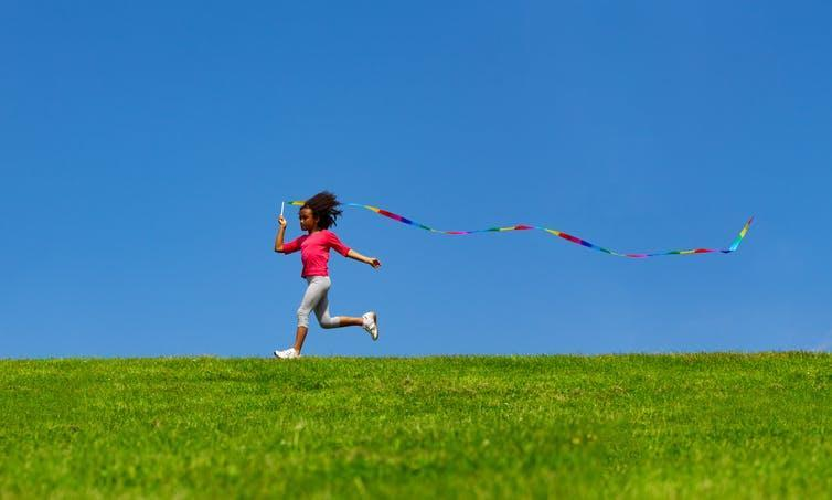 Young girl running on grass with a ribbon flowing out behind her against a bright blue sky.