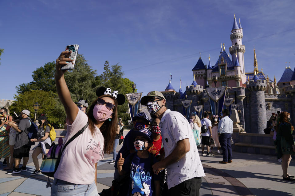 FILE - In this April 30, 2021, file photo, a family takes a photo in front of Sleeping Beauty's Castle at Disneyland in Anaheim, Calif. A number of states immediately embraced new guidelines from the CDC that say fully vaccinated people no longer need to wear masks indoors or out in most situations. But other states - and some businesses _ are taking a wait-and-see attitude. (AP Photo/Jae Hong, File)