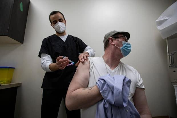 Pharmacist Kyro Maseh administers a dose of the AstraZeneca COVID-19 vaccine to Matthew Stone, 46, at a pharmacy in Toronto on Apr. 20, 2021.