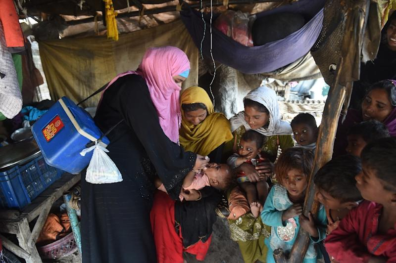 A Pakistani health worker administers drops to a child during a polio vaccination campaign in Lahore