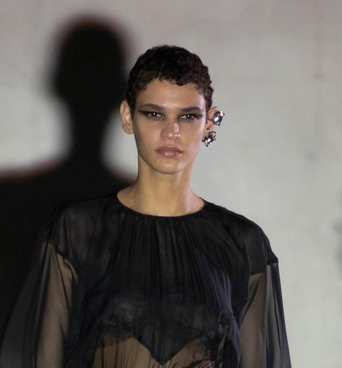 <p>The smoky black shadow at No. 21 gave us flashbacks to the edgy fall beauty moments at NYFW. Makeup artist Luciano Chiarello added sharp wings flicking out past the tails of the models' brows of onyx with accents of metallic graphite on their inner corners. The result was a stunning, modern goth look.</p> <p>Hairstylist Paolo Soffiatti, on the other hand, added a ruffled-up effect to the models' natural hair textures. </p>