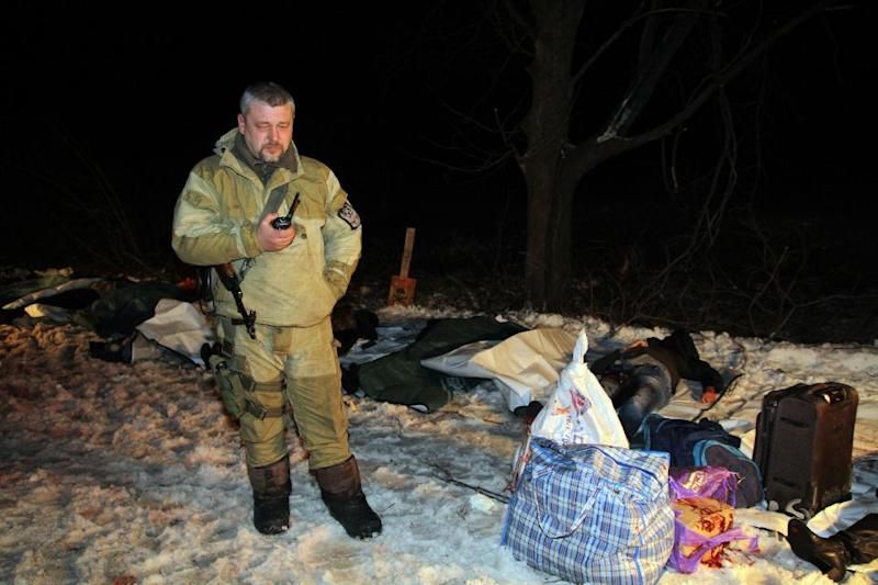 The bodies of passengers killed on a bus that was hit during shelling apparently aimed at a checkpoint manned by Ukrainian forces in Volnovakha, in the eastern Donetsk region, are laid out on body bags on January 13, 2015 (AFP Photo/Alexander Gayuk)