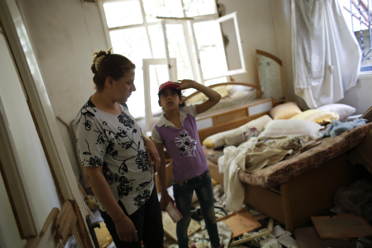 In this May 18, 2017 photo, Adibeh Ghosn and her daughter Samar survey damage inside their house at the mountain resort town of Zabadani in the Damascus countryside, Syria. Once a popular summer resort famed for its fruit trees and favored by tourists from rich Gulf Arab countries, Zabadani is now a deserted, endless vista of pulverized buildings after thousands of rebels were driven out along with the town's original inhabitants. (AP Photo/Hassan Ammar)