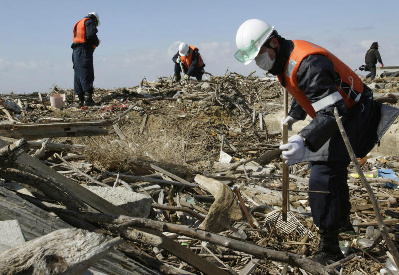 Police officers search for the remains of those who went missing in the March 11, 2011 tsunami on the coastline in Ishinomaki, Miyagi Prefecture, northern Japan, Monday, March 11, 2013. The two-year anniversary Monday of Japan's devastating earthquake, tsunami and nuclear catastrophe is serving to spotlight the stakes of the country's struggles to clean up radiation, rebuild lost communities and determine new energy and economic strategies.(AP Photo/Shizuo Kambayashi)