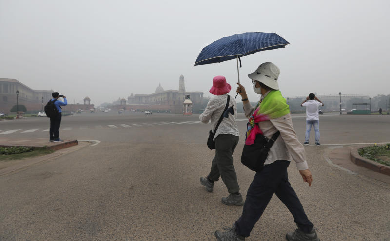 Foreign tourists wear pollution masks and walk at Raisna hills, enveloped by smog in New Delhi, India, Thursday, Nov. 7, 2019. The air quality index stood at 273 on Thursday in the capital after authorities declared a health emergency last weekend when the index crossed 500 — 10 times the level considered healthy by WHO standards. (AP Photo/Manish Swarup)